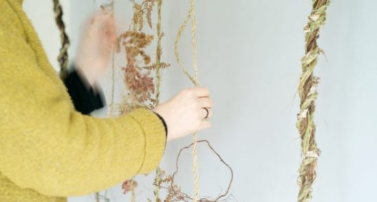 Caroline Dear works on a piece for a wall hanging on info page